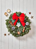 Weihnachtskranz aus Nadelzweigen dekoriert mit Zapfen, Zimtstangen und roter Schleife