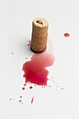 Cork and red wine splatter on white background