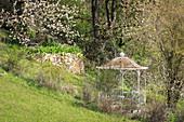 Hanggarten mit Pavillon, Trockenmauer und blühendem Apfelbaum