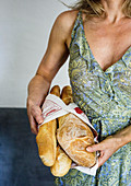French lady holding baguettes and French bread