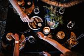 Hände greifen nach Essen auf dem Tisch