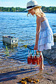 Girl holding drinks at water