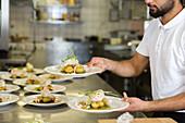 Koch hält Teller mit Essen in einer Restaurantküche