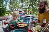 Kleines Mädchen und Vater sitzen am Tisch beim Essen