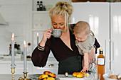 Mutter mit Kleinkind im Arm trinkt Kaffee