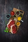 Various barbecue sauces alongside fresh rump steaks