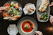 Salad, tomato soup and omelette on plates
