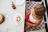 "Girl having pancake with ""smiley"" on plate"