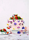 Strawberry buttercream cake decorated with edible flowers