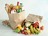 Two shopping bags with different groceries and fruits and vegetables
