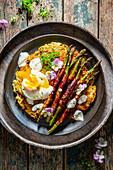 Potato pancakes with bacon, asparagus and a baked egg