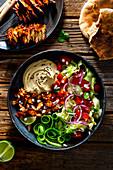 Vegetarian kebab with vegetable salad and hummus