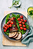 Rolled pork roast with roasted tomatoes and broccolini