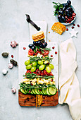 Christmas cheese platter with grapes, cucumber, and crackers in the shape of a fir tree