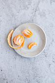 Peeled Honeygold mandarin on decorative ceramic plate