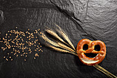 Pretzel next to cereal ears and cereal grains