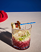Alcohol-free pastis with cherry juice, with skewers with merguez, cheese, and fig