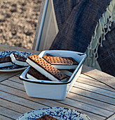 An outdoor table with an enamel tin filled with chocolate and vanilla ice cream sandwiches