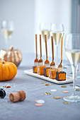 Pumpkins aper cubes on golden forks with poppy seeds and champagne glasses