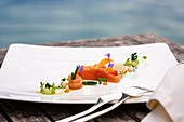 Char dish served on wooden table overlooking a lake
