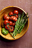 Tomatoes and asparagus in earthenware bowl