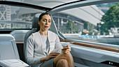 Woman using a tablet in an autonomous car