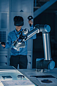 Engineer controlling robotic arm with VR headset