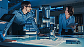 Engineers analysing a robotic arm