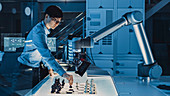 Engineer playing chess with a robotic arm