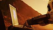 Astronaut using a laptop on alien planet