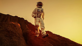 Astronaut descending from a mountain on a red planet