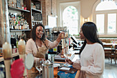 Bartender serving young woman in pub