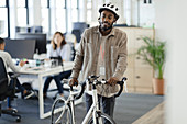 Man walking with his bicycle in an office