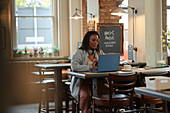 Woman working on a laptop at cafe table