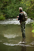 Man with backpack fly fishing at river