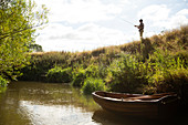 Man fly fishing on a riverbank