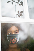 Woman in face mask at window