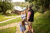 Family walking on path above cabin in woods