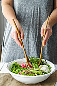 Female hands using wooden salad spoons to toss fresh spring salad