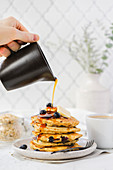 Hand pouring maple syrup on a stack of blueberry pancake