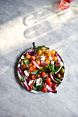 A healthy Tomato Salad against a marble background