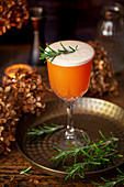 A rosemary infused Sour cocktail topped with egg white foam and a rosemary sprig