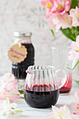 Blackcurrant cordial in a jug with some poured into a glass in the background ready for diluting with water