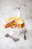 Rhabarberkuchen mit Baiser, angeschnitten auf Kuchenständer