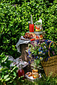 Picnic set on a stump with a bunch of wildflowers, salad in jars