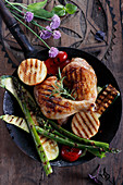 Grilled chicken and vegetables on a dark wooden table