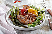 Grilled pork neck with pepper, asparagus and onion