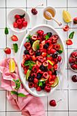 Fruit salad of strawberries, cherries, blackberries, raspberries lime and fresh mint