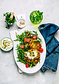 Potato and zucchini hash browns with quark cream and rocket salad