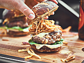 Cheeseburger with crispy fried onions on a Pretzel bun.